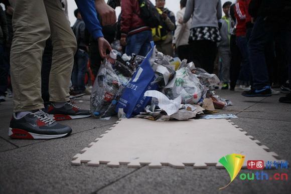 国庆天安门升旗仪式后废纸遍地 大学生自发捡垃圾受赞