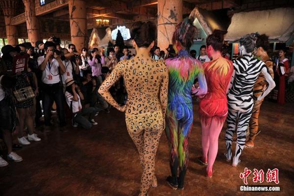 三亚动物园美女人体彩绘与动物互动 扮斑马长颈鹿吸引