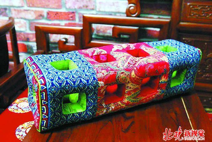 许崇有就是一位玲珑枕的制作者,他和妻子在后海北沿的家里兢兢业业地手工制作着玲珑枕。夫妻二人有分工、有合作,两人创意、设计、配色有商有量,之后许崇有负责把布料剪裁备好,而缝制一般就由妻子完成。由于许崇有家里的玲珑枕都是纯手工制作,耗时长,费工夫,缝制一个最快也要三天的时间。 许崇有告诉我,他家的玲珑枕手艺是从宫中传出来的,现在已经传到了第四代,我从小就跟父母学,学这个需要眼睛好,心细,你得一针一针缝啊,不能有半点马虎。这玲珑枕用的也都是上好的面料,有云锦、织锦缎等,云锦一米就要2800块钱,容不得半点浪