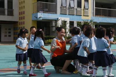 红黄蓝幼儿园老师带着孩子们在进行欢快的户外活动