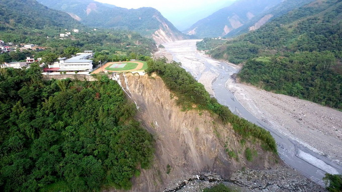 从拍照的角度看去,只见一所小学的操场紧邻崩塌山体.